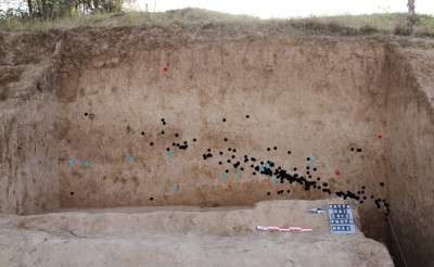 Figure 4. Longitudinal cross section of the Katta Sai site with location of artefacts. Black dots: stone artefacts; blue: mollusc shells; red: pottery. Photograph by Małgorzata Kot.